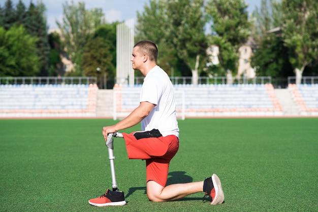 フィールドのスタジアムで突進をしている義足を持つ若い白人ブルネットの男性。スポーツコンセプト