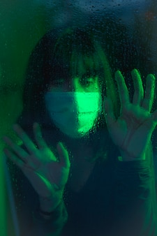 A young caucasian brunette with face mask looking into the covid19 quarantine, with green ambient light