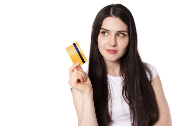 Молодая кавказская брюнетка в белой футболке демонстрирует свою кредитную карту золотого банка для макета