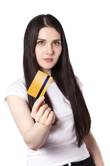 Молодая кавказская брюнетка в белой футболке держит кредитную карту золотого банка для макета вертикали