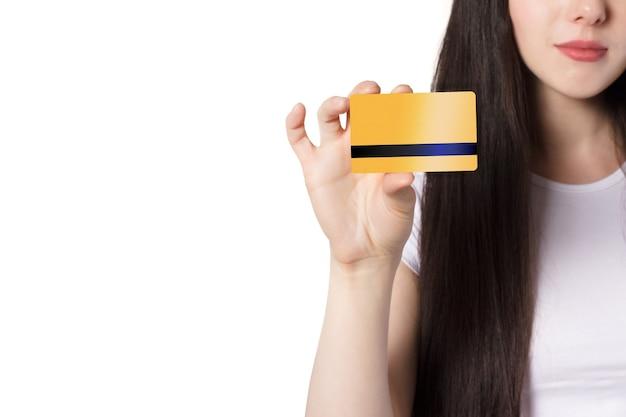 흰색 티셔츠를 입은 젊은 백인 갈색 머리 여성이 모의를 위해 금 은행 신용 카드를 들고 있습니다.