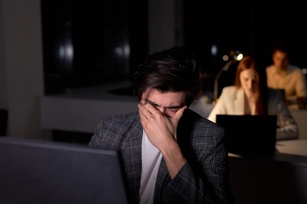 양복을 입은 젊은 백인 브루넷 남자는 밤에 사무실에 앉아 있고, 눈은 과로로 다치고 두통으로 고통받고 있습니다. 남자 회사원은 기한을 지키지 않습니다. 복사 공간