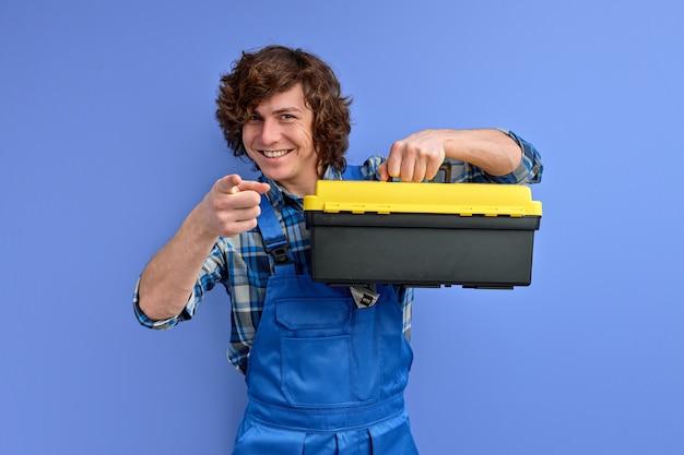 作業服の若い白人ビルダーの男は、スタジオで隔離のツールボックスを保持します