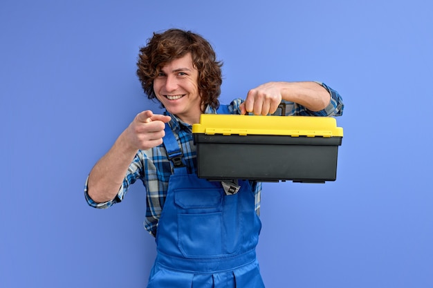Young caucasian builder man in workwear holds tool box isolated in studio