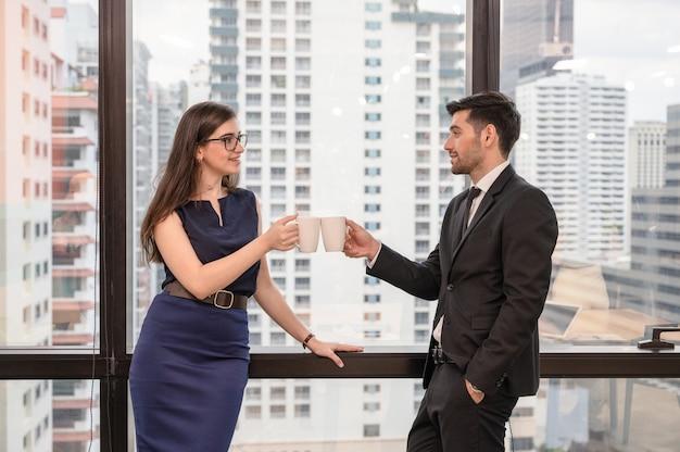 オフィスで若い白人ビジネス部門の同僚を保持し、乾杯のコーヒーカップ