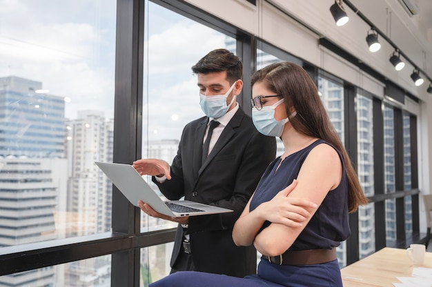 Young caucasian business colleague wearing face mask discussing with laptop in new normal office at business district