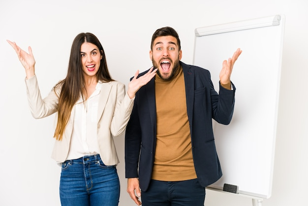 若い白人のビジネスカップルは、嬉しい驚きを受け取り、興奮し、手を上げて孤立しました。