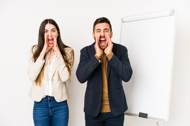 Young caucasian business couple isolated shouting excited to front.