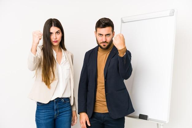 Молодые кавказские бизнес-пара изолированы, показывая кулак, агрессивное выражение лица.