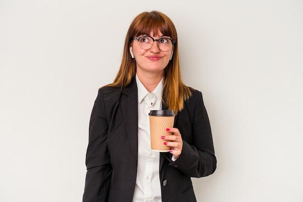 目標と目的を達成することを夢見て白い背景で隔離のコーヒーを保持している若い白人ビジネス曲線美の女性