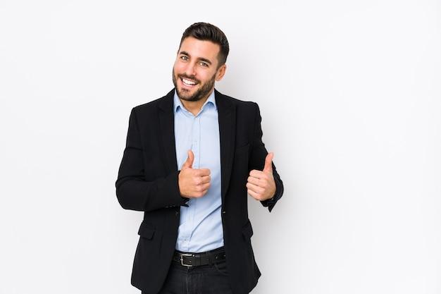 白い背景に対して若い白人のビジネスマンは両方の親指を上げて、笑顔で自信を持って分離しました。