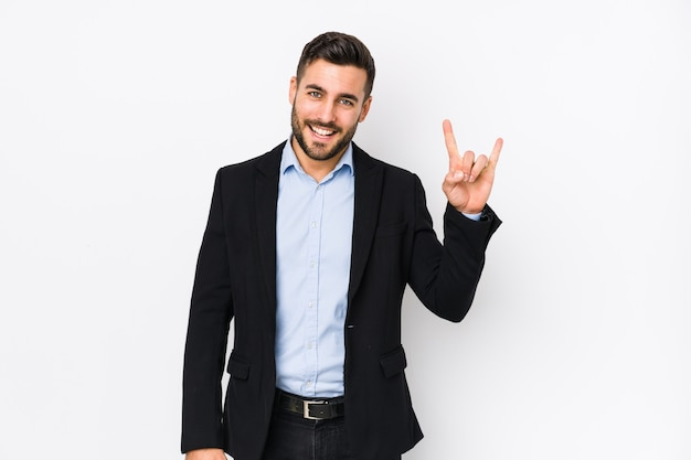 Young caucasian business man against a white background isolated showing a horns gesture as a revolution concept.