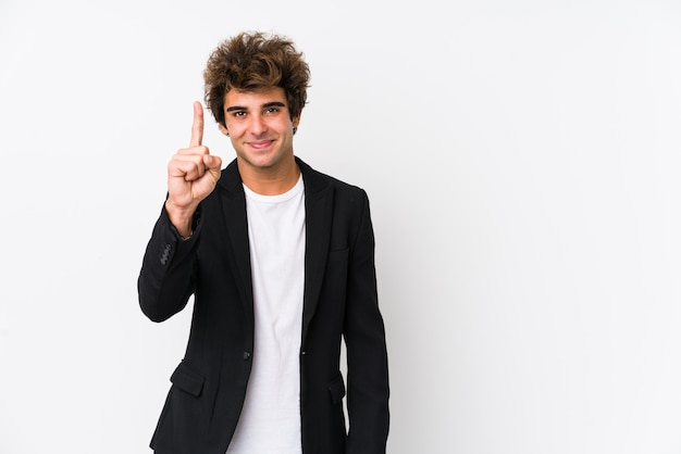 Young caucasian business man against a white wall isolated showing number one with finger.