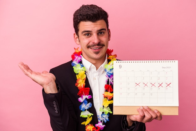 Young caucasian business man counting the days for vacations isolated on pink background showing a copy space on a palm and holding another hand on waist.