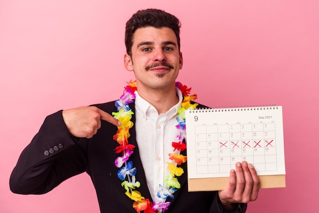 ピンクの背景に孤立した休暇の日を数える若い白人ビジネスマンが、シャツのコピースペースを手で指し、誇りと自信を持って