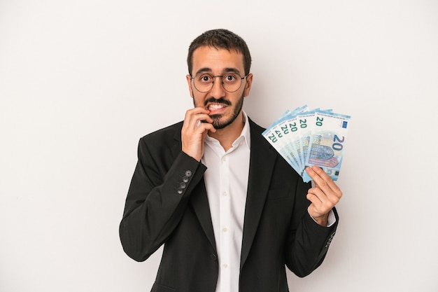 指の爪を噛んで、神経質で非常に心配している白い背景で隔離された紙幣を保持している若い白人ビジネスマン。