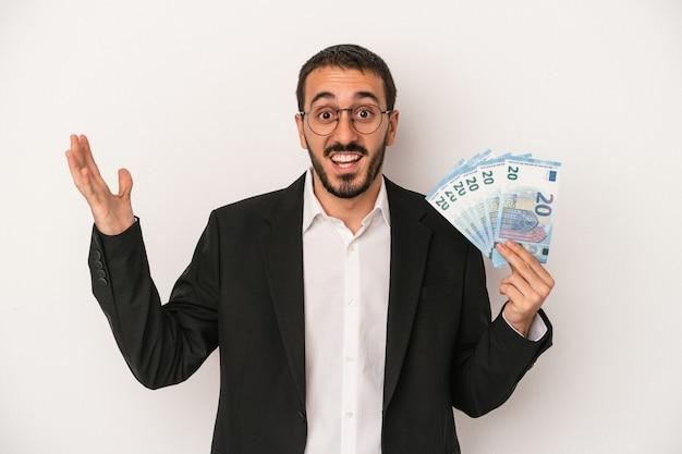 白い背景で隔離の紙幣を保持している若い白人ビジネスマンは、嬉しい驚きを受け取り、興奮し、手を上げます。