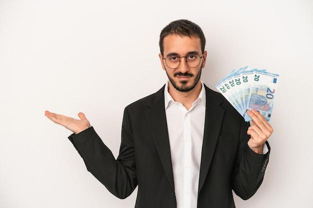 手のひらにコピースペースを示し、腰に別の手を保持している白い背景で隔離の紙幣を保持している若い白人ビジネスマン。