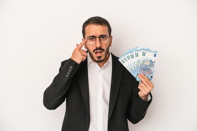 人差し指で失望のジェスチャーを示す白い背景で隔離の紙幣を保持している若い白人ビジネスマン。