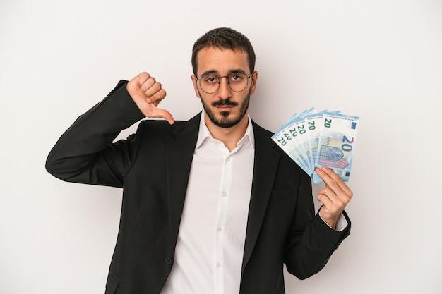 嫌いなジェスチャーを示す白い背景に分離された紙幣を持っている若い白人ビジネスマンは、親指を下に向けます。不一致の概念。