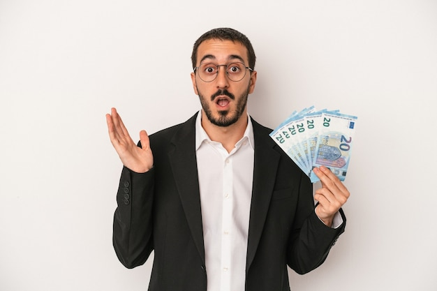 白い背景で隔離の紙幣を保持している若い白人ビジネスマンは驚いてショックを受けました。