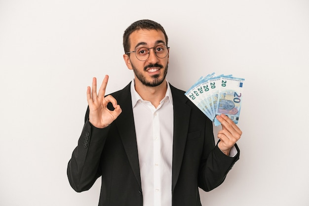 Young caucasian business man holding banknotes isolated on white background cheerful and confident showing ok gesture.