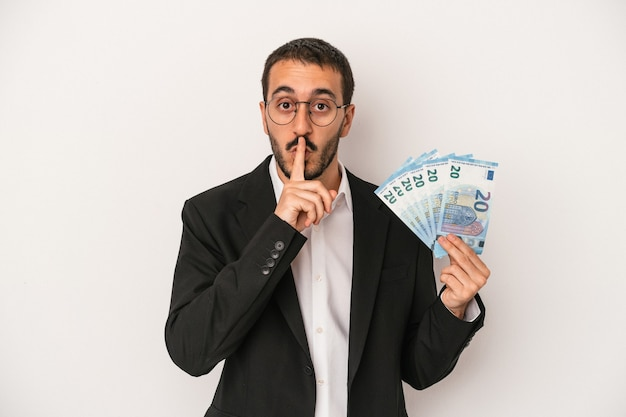 Young caucasian business man holding banknotes isolated on white background keeping a secret or asking for silence.