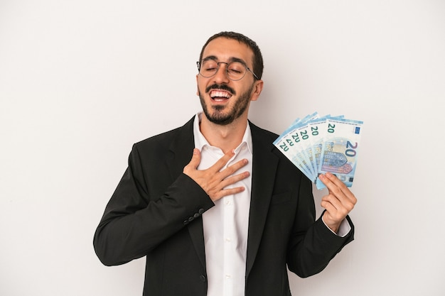 Young caucasian business man holding banknotes isolated on white background laughs out loudly keeping hand on chest.