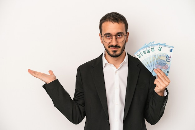 Young caucasian business man holding banknotes isolated on white background showing a copy space on a palm and holding another hand on waist.