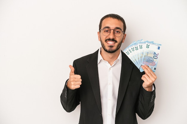 Young caucasian business man holding banknotes isolated on white background smiling and raising thumb up