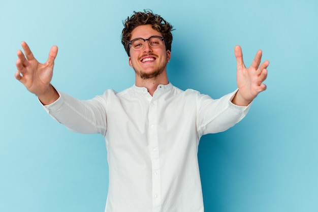 Young caucasian business man isolated on blue background feels confident giving a hug to the camera.