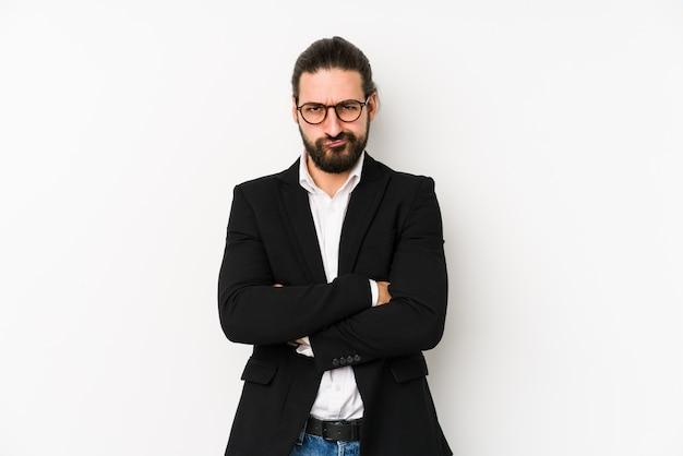 Молодой кавказский деловой человек, изолированные на белом фоне, недовольно хмурясь, держит руки сложенными.