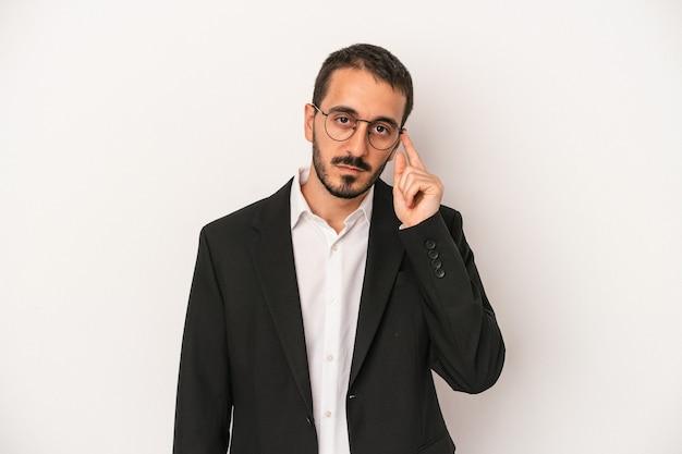 指で寺院を指して、思考、タスクに焦点を当てて、白い背景で隔離の若い白人ビジネスマン。
