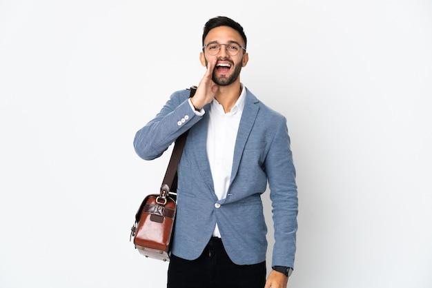Молодой кавказский деловой человек, изолированные на белом фоне, кричит с широко открытым ртом