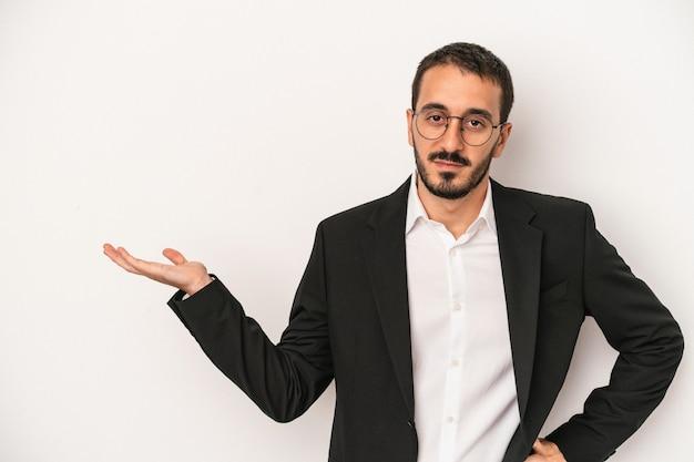 手のひらにコピースペースを示し、腰に別の手を保持している白い背景で隔離の若い白人ビジネスマン。