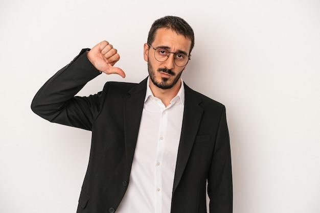 嫌いなジェスチャーを示す白い背景に分離された若い白人ビジネスマンは、親指を下に向けます。不一致の概念。