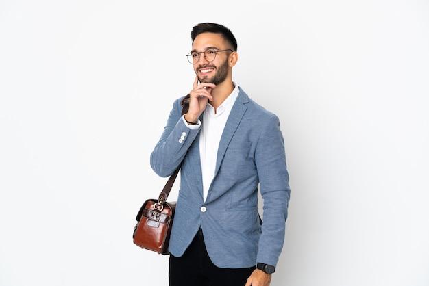 Молодой кавказский деловой человек изолирован на белом фоне, думая об идее, глядя вверх