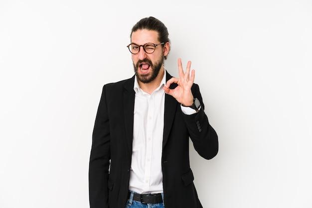 Молодой кавказский деловой человек, изолированный на белом, подмигивает и держит рукой нормальный жест.