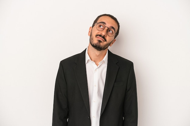 Young caucasian business man isolated on white background dreaming of achieving goals and purposes