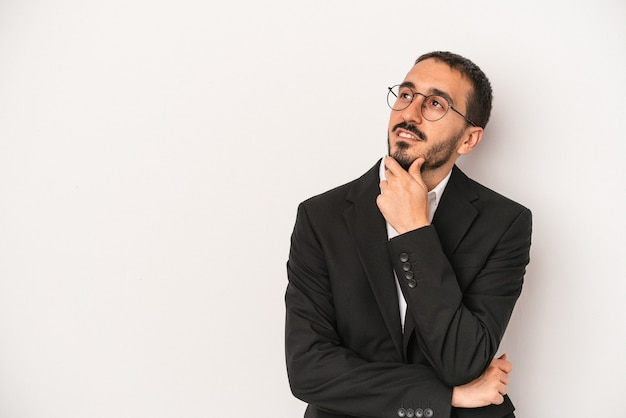 Young caucasian business man isolated on white background looking sideways with doubtful and skeptical expression.