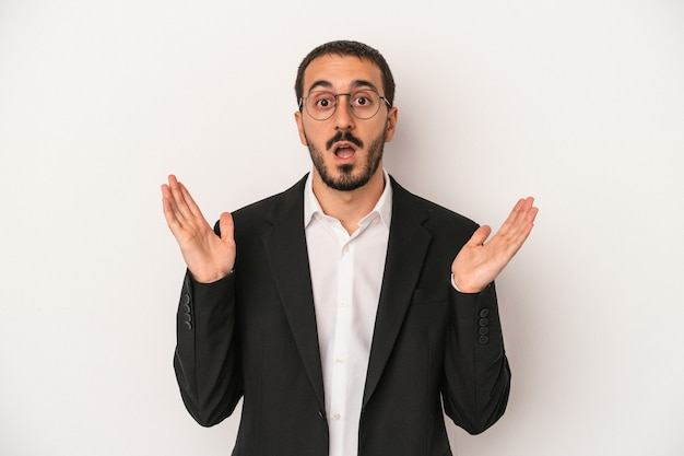 Young caucasian business man isolated on white background surprised and shocked.