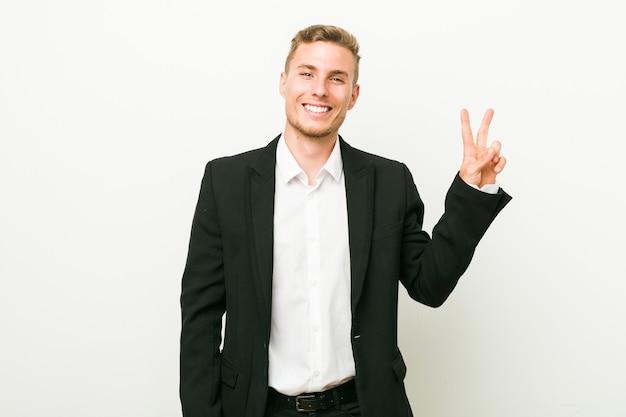 指で平和のシンボルを示す、楽しくてのんきな若い白人ビジネスマン。