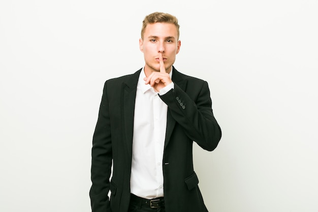 Young caucasian business man keeping a secret or asking for silence.