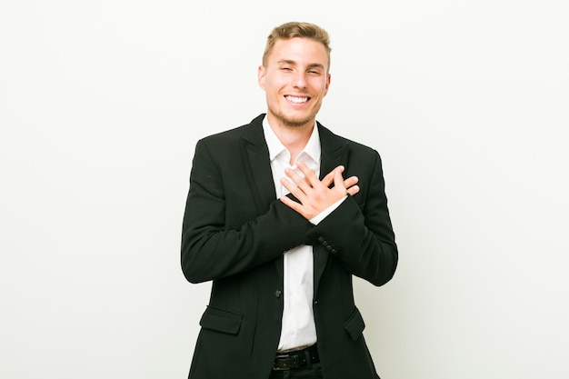 Young caucasian business man laughing keeping hands on heart, concept of happiness.