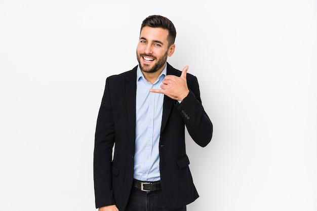 Молодой кавказский деловой человек на белом изолированном показывая жест звонка мобильного телефона с пальцами.