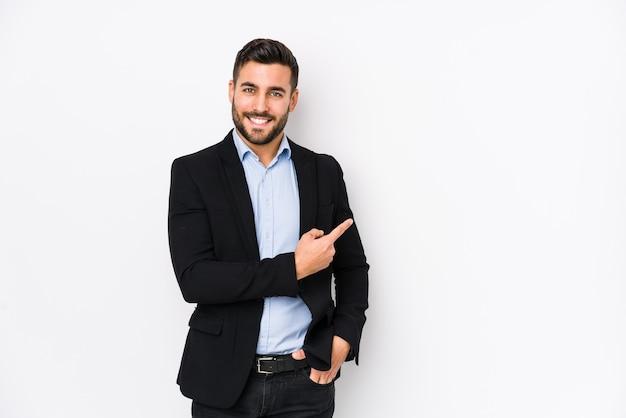 Молодой кавказский деловой человек на белом изолировал, улыбаясь и указывая в сторону, показывая что-то на пустом месте.