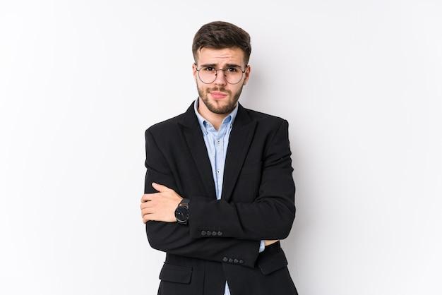 Молодой кавказский деловой человек позирует в белом изолированном фоне молодой кавказский деловой человек, нахмурившись лицом в неудовольствие, держит руки сложенными.