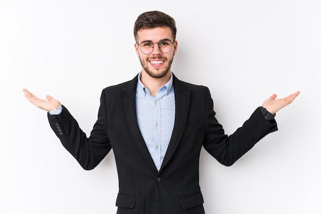 分離した白い背景でポーズをとって若い白人ビジネスマン若い白人ビジネスマンは腕でスケールを作る、幸せと自信を感じています。