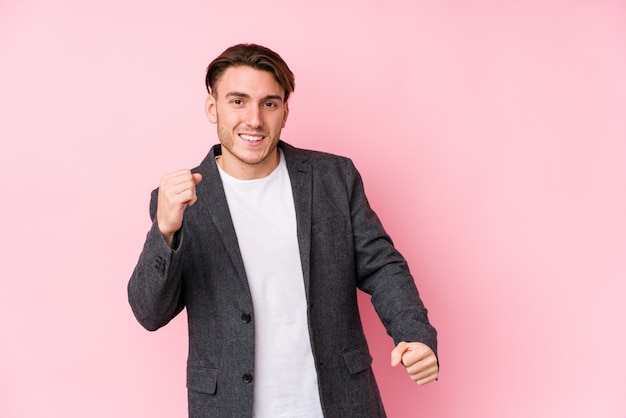Young caucasian business man posing isolated dancing and having fun.