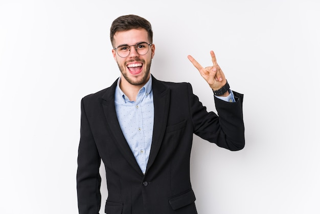Young caucasian business man posing in a white background isolated young caucasian business man showing a horns gesture as a revolution concept.